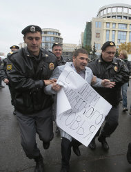 "Police detain an Orthodox believer carrying a protest poster outside a court in Moscow, Wednesday. Oct. 10, 2012. Three members of the punk band Pussy Riot are set to make their case before a Russian appeals court that they should not be imprisoned for their irreverent protest against President Vladimir Putin. The poster reads in Cyrillic : ""Congratulations With a Day of Psychological sanity"". (AP Photo/Mikhail Metzel)"