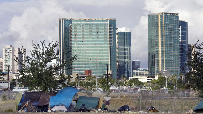 FILE - In this Monday, July 12, 2010 file photo, the Honolulu skyline rises behind a homeless camp in an empty lot near Kaakako Park, in Honolulu. Homelessness increased 15 percent on Oahu since last year according to a recent report. A growing number of homeless are not from Hawaii but make the most of their situation by taking advantage of inviting beaches and support services. State lawmakers are struggling with the visible problem of homelessness in tourist areas and some have proposed a contentious idea to use state money to fly the homeless back to wherever they came from. (AP Photo/Marco Garcia, File)