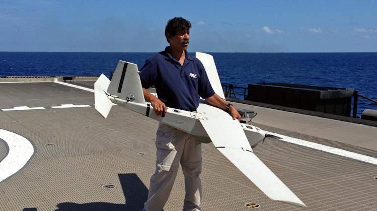 Stuart Orozco, flight operator with Aeronvironment Inc., prepares lo launch a UAS (unmanned aircraft system) named Puma from the deck of the U.S. Navy high speed vessel Swift near Key West, Florida, Friday, April 26, 2013. The U.S. Navy on Friday began testing two new aerial tools, borrowed from the battlefields of Afghanistan and Iraq, that officials say will make it easier to detect, track and videotape drug smugglers in action. (AP Photo/Ben Fox)