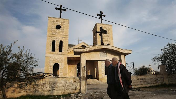 In this Thursday, Feb. 21, 2013 photo, Syrian citizens walk in front of a church that was shelled by mortars, at the Christian village of Judeida, in Idlib province, Syria. Yacobiyeh and its neighbors, Judeida and Quniya, are some of the first Christian villages to be taken by the rebel Syrian Army. The rebels stormed these hilltop villages in late January, after the army used it as a base to shell nearby rebel-controlled areas. The villages are largely empty due to the fighting, with a few mostly elderly Christians -- including Roman Catholics and Armenian Orthodox _ living among Sunni Muslim refugees who have moved up here from the plains. They still face sporadic artillery bombardment from below. (AP Photo/Hussein Malla)