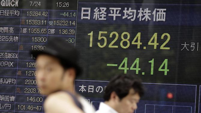Men walk by an electronic stock board of a securities firm in Tokyo, Thursday, July 24, 2014. Asian shares were subdued Thursday despite an improvement in China's manufacturing as a wait-and-see mood prevailed ahead of earnings reports from some of the region's top companies. (AP Photo/Eugene Hoshiko)