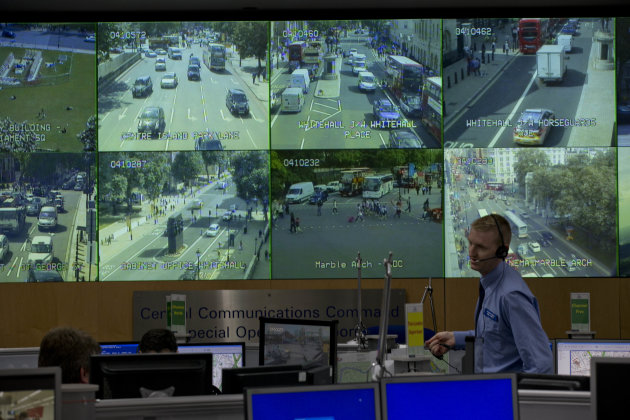 A member of police staff stands in front of CCTV screens in London's Metropolitan Police Service Special Operations Room in central London, Thursday, July 19, 2012. The room will be the police control room for the Olympic Games in the capital and is equipped with technology essential to the smooth running of the policing operation. This includes screens on which CCTV can be shown to provide views across the city. (AP Photo/Matt Dunham)
