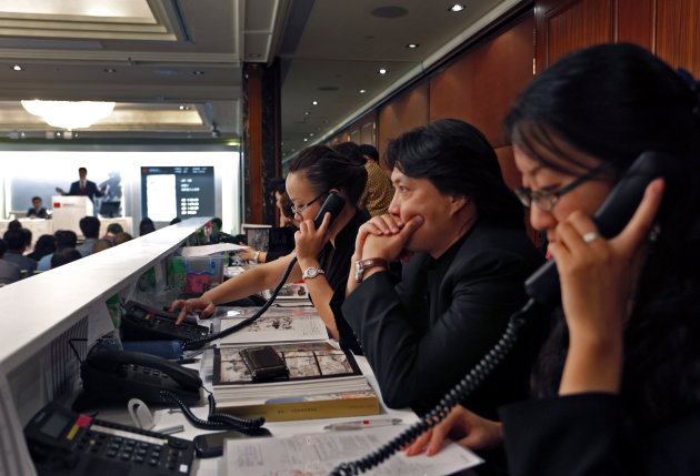 Staff members listen to collectors&#39; offers on the phone during the autumn sale of China Guardian Auctions Co., in Hong Kong Sunday, Oct. 7, 2012. Chinese and international auction houses are encroaching on each other&#39;s territory in Hong Kong and Beijing for the first time this autumn sale season as they step up the battle for the Asian art market. (AP Photo/Vincent Yu)