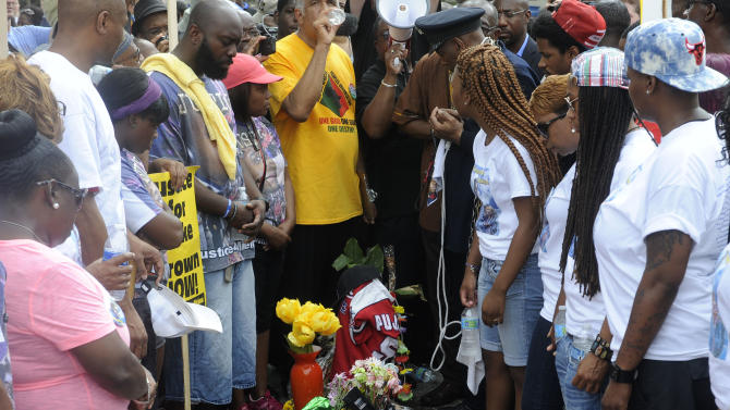 Family members of Michael Brown, an unarmed black 18-year-old who was fatally shot by a white police officer three weeks earlier, have a moment of silence at the site of the shooting in Ferguson, Mo. on Saturday, Aug. 30, 2014. Fifth from left is his father, Michael Brown Sr., with towel, and mother, Lesley McSpadden, third from right. (AP Photo/Bill Boyce)
