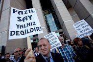 "A supporter of world-renowned Turkish pianist Fazil Say holds a placard reading ""Fazil Say is not alone"" during a protest held outside an Istanbul court on October 18. The 42-year-old virtuoso, who has played with the philharmonic orchestras of Berlin, New York, Tokyo and Israel, is charged with inciting religious hatred and insulting Islamic values in a series of provocative tweets"