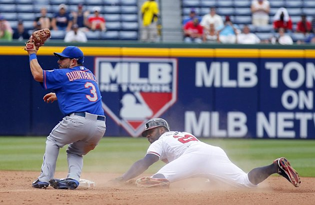 New York Mets shortstop Omar Quintanilla (3) holds up the ball after tagging out Atlanta Braves Jason Heyward trying to steal second base in the seventh inning of the first baseball game of a doublehe