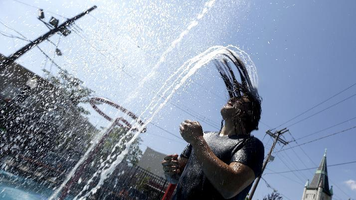 Javier Soler, 20, of West New York, N.J., flips his head back as water from a fountain runs off his hair during a heat wave, Thursday, July 18, 2013, in Union City, N.J. (AP Photo/Julio Cortez)
