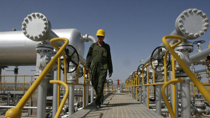 FILE - In this Tuesday, April 15, 2008 file photo Iranian oil technician Majid Afshari makes his way to the oil separator facilities in Iran's Azadegan oil field southwest of Tehran, Iran. The market is so flush with oil at the moment that even the loss of more Iranian crude from the market may not lead to short supplies and higher prices. In fact, if Iran figures out a way to get around the sanctions and get more of its oil to market, oil prices could fall further. (AP Photo/Vahid Salemi, File)