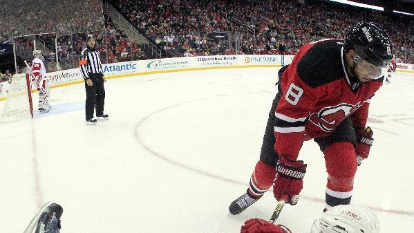 In this photograph taken with a fisheye lens, New Jersey Devils right wing Dainius Zubrus (8), of Lithuania, and Detroit Red Wings defenseman Kyle Quincey (27) get tangled up in the corner during the second period of an NHL hockey game, Friday, Nov. 28, 2014, in Newark, N.J. (AP Photo/Julio Cortez)