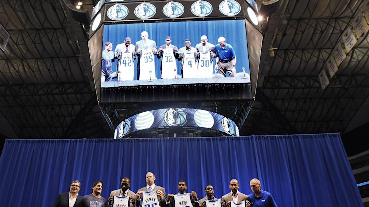 Dallas Mavericks general manager Donnie Nelson, left, owner Mark Cuban, second from left, and head coach Rick Carlisle, right, pose with Elton Brand (42), Chris Kaman (35), O.J. Mayo (32), Darren Collison (4) and Dahntay Jones (30) during an NBA basketball news conference introducing the new players at American Airlines Center in Dallas, Monday, Sept. 10, 2012. (AP Photo/LM Otero)