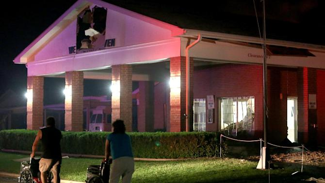 Persons are seen pushing wheel chairs in front of a damaged nursing home following an explosion at a nearby fertilizer plant Wednesday, April 17, 2013, in West, Texas. An explosion at a fertilizer plant near Waco caused numerous injuries and sent flames shooting high into the night sky on Wednesday.(AP Photo/ Waco Tribune Herald, Rod Aydelotte)