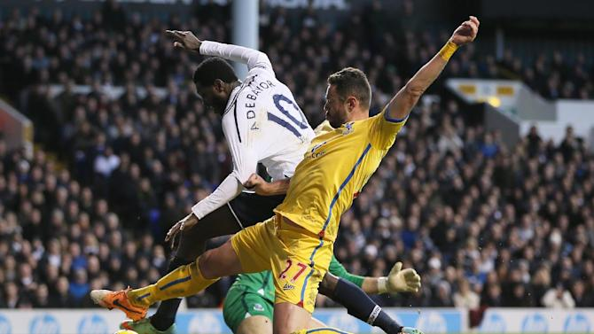 Tottenham's Emmanuel Adebayor, behind, attempts to shoot at goal as he is tackled by Crystal Palace's Damien Delaney during their English Premier League soccer match at the White Hart Lane stadium in London, Saturday, Jan.11, 2014