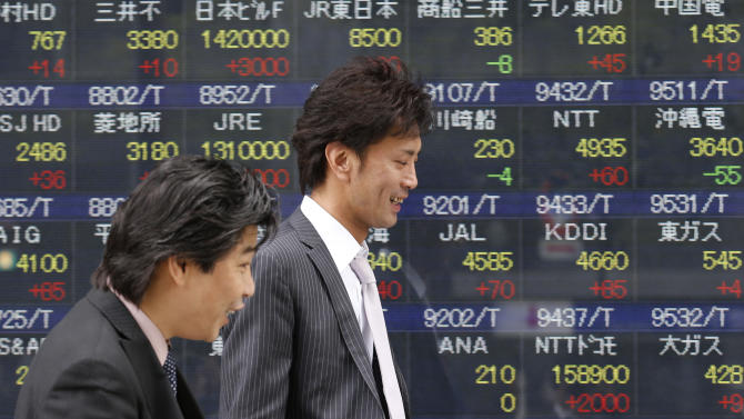 People walk by an electronic stock board of a securities firm in Tokyo, Thursday, April 25, 2013. Asian stocks rose Thursday as mixed U.S. corporate earnings and a slump in orders for U.S. durable goods convinced investors that central banks would continue efforts to help the global economic recovery. Japan's Nikkei 225 rose 0.5 percent to 13,909.40. (AP Photo/Koji Sasahara)
