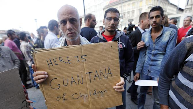 An sylum-seeker shows a sign in front of Keleti railway station in Budapest, Hungary, Friday, Sept. 4, 2015. Over 150,000 people seeking to enter Europe have reached Hungary this year, most coming through the southern border with Serbia, and many apply for asylum but quickly try to leave for richer EU countries. (AP Photo/Frank Augstein)