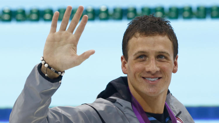 United States' Ryan Lochte wears his gold medal as he waves to spectators after the medal ceremony for men's 400-meter individual medley swimming final at the 2012 Summer Olympics, Saturday, July 28, 2012, in London. (AP Photo/Daniel Ochoa De Olza)