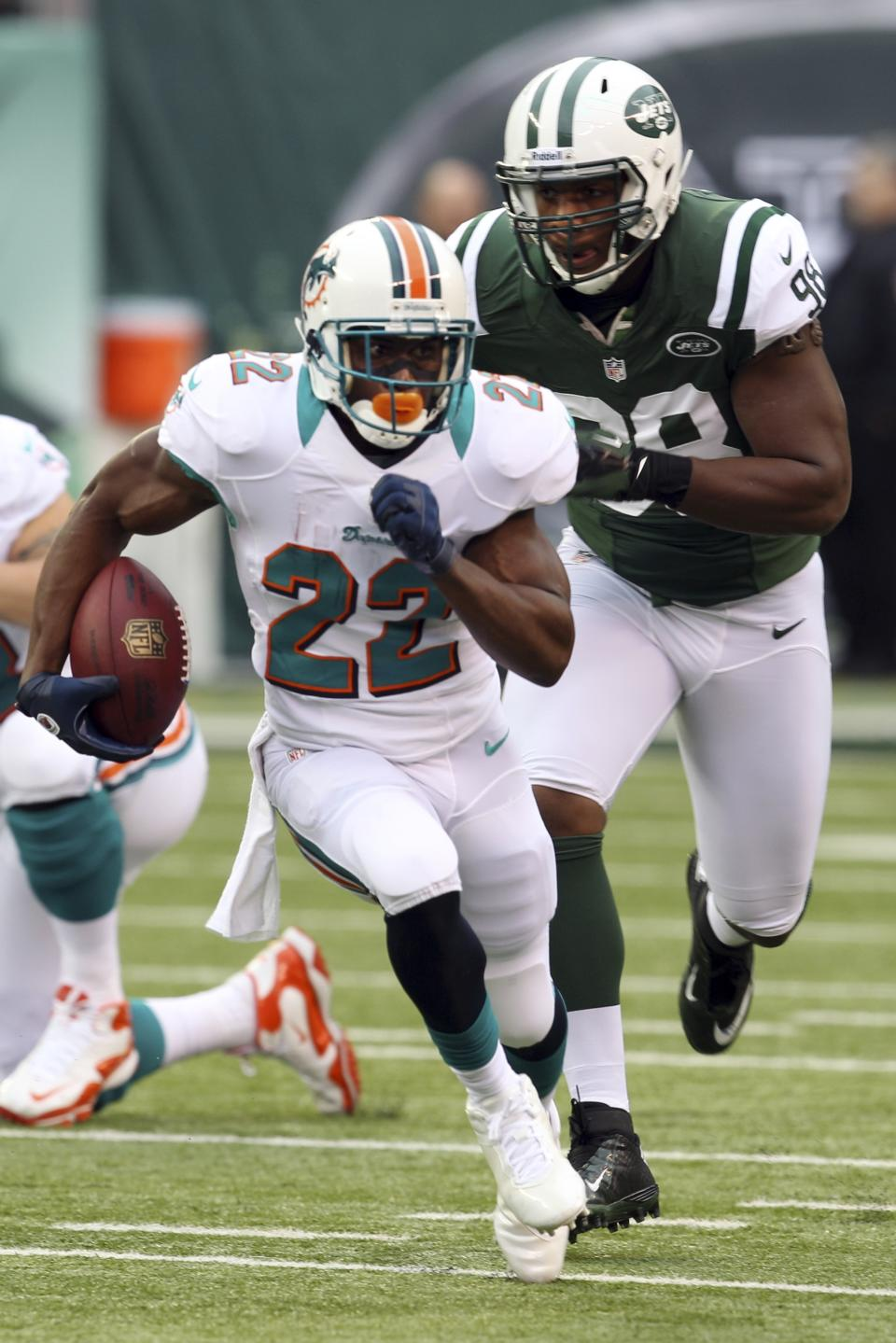 Miami Dolphins running back Reggie Bush (22) runs away from New York Jets defensive end Quinton Coples (98) during the first half of an NFL football game Sunday, Oct. 28, 2012 in East Rutherford, N.J. (AP Photo/Seth Wenig)
