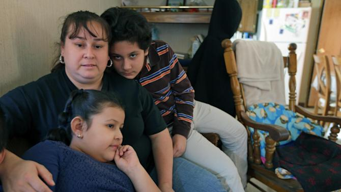 In this Feb. 28, 2013 photo, Sarah Chavez, center, sits with her son Bidal, right, and daughter Sarahi, front, at her home in Lexington, N.C. Desperate to raise money for their 6-year-old daughter's cancer treatments last summer, friends told Jose and Sarah Chavez of a way to quickly turn their meager savings into a small fortune. But what the Chavez family and many others didn't know was that state and federal regulators for months had received complaints that ZeekRewards was a scam. (AP Photo/Chuck Burton)