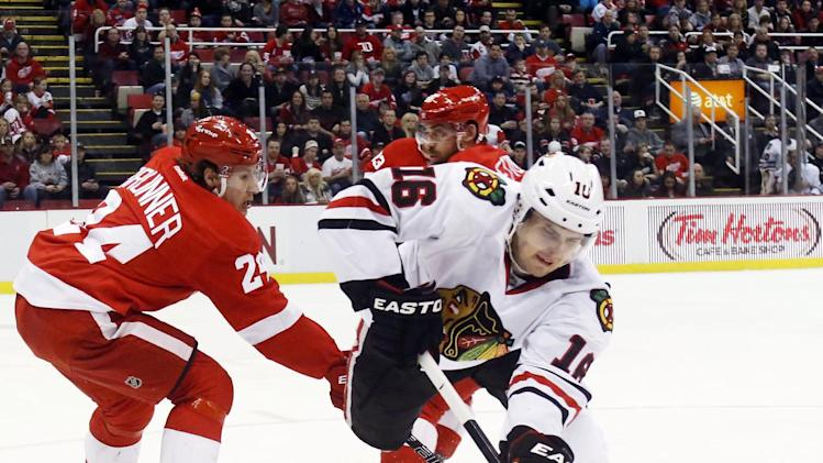 Chicago Blackhawks center Marcus Kruger (16), of Sweden, tries to keep the puck away from Detroit Red Wings center Damien Brunner (24) in the first period of an NHL hockey game on Sunday, March 3, 2013, in Detroit. (AP Photo/Duane Burleson)