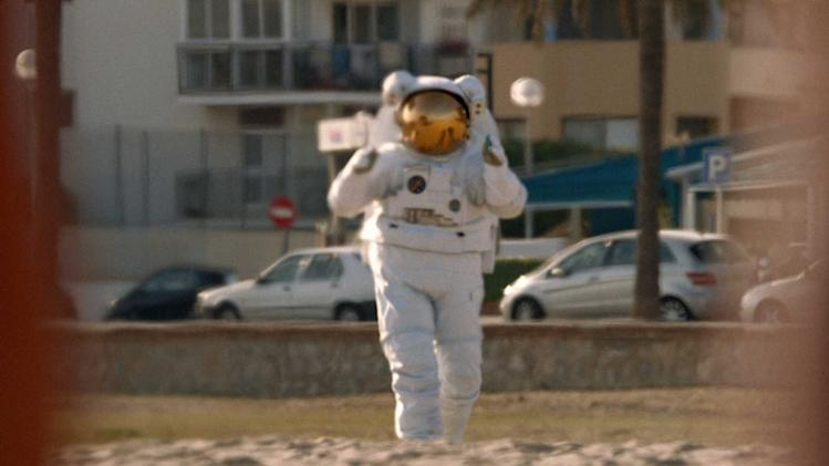 """This undated screenshot provided by Axe shows the Super Bowl advertisement for Axe. Axe's 30-second ad in the third quarter of the game shows a woman in the ocean getting rescued by a sexy lifeguard, but going for an astronaut instead. It promotes Axe's new cologne """"Apollo"""" and its contest to send someone on the first suborbital space tour in 2014. (AP Photo/Axe)"""