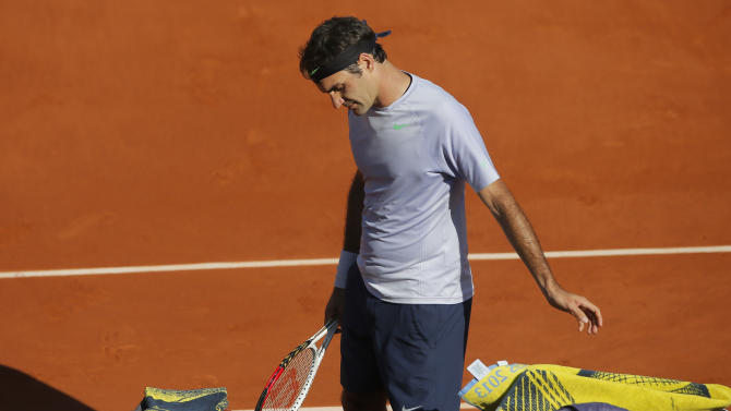 Switzerland's Roger Federer looks down during a break as he plays France's Jo-Wilfried Tsong74during their quarterfinal match of the French Open tennis tournament at the Roland Garros stadium Tuesday, June 4, 2013 in Paris. Tsonga won 7-5, 6-3, 6-3. (AP Photo/Michel Spingler)