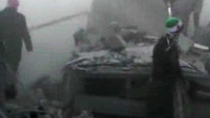 In this image taken from video obtained from Bambuser, which has been authenticated based on its contents and other AP reporting, Syrians stand at the scene after an airstrike hit Douma City, Syria on Thursday, Jan. 3, 2013. Airstrikes continued across Syria on Thursday as Syrian President Bashar Assad's military stepped up its assault on areas that surround the nation's capital. (AP Photo/Bambuser via AP video)