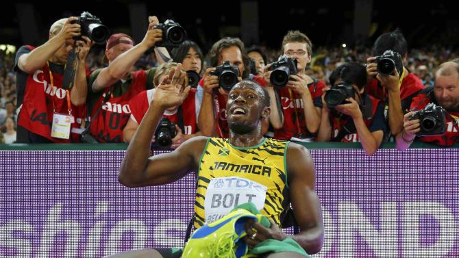 Bolt of Jamaica poses for photographers after winning the men's 200 metres final during the 15th IAAF World Championships at the National Stadium in Beijing