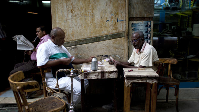 Two Egyptian men play cards at a local coffee shop in downtown Cairo, Egypt, Wednesday, Oct. 31, 2012. Egypt's capital prides itself on being city that never sleeps, with crowds filling cafes and shops open into the small hours. So the government is facing a backlash from businesses and the public as it vows to impose new nationwide rules closing stores and restaurants early. Officials say the crisis-ridden nation has to conserve electricity, but they also seem intent on taming a population they see as too unruly. (AP Photo/Nasser Nasser)