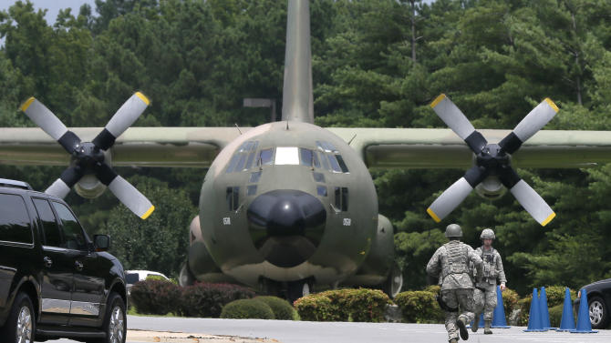 Security personnel run past a C-130 aircraft on static display at the front gate of Little Rock Air Force Base in Jacksonville, Ark., Wednesday, July 23, 2014. The base has been on lockdown since late morning Wednesday. (AP Photo/Danny Johnston)