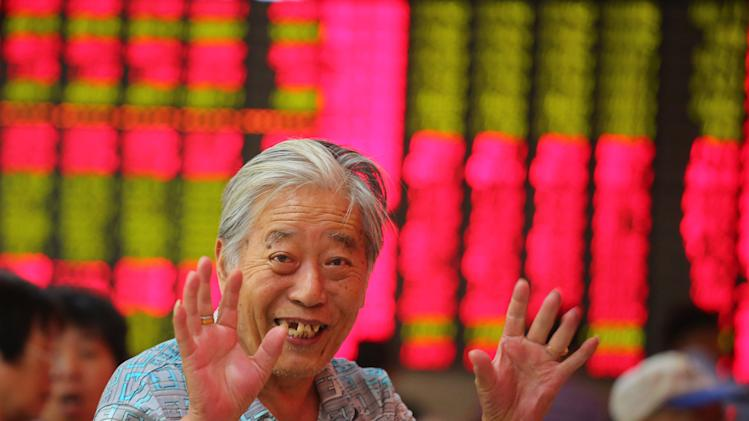 An investor gestures at a private securities company in Shanghai, China, Thursday, July 18, 2013. Asian stocks were mostly higher Thursday, tracking overnight gains in Europe and Wall Street after U.S. Federal Reserve chairman Ben Bernanke's suggested stimulus policies may continue for longer than expected. (AP Photo)