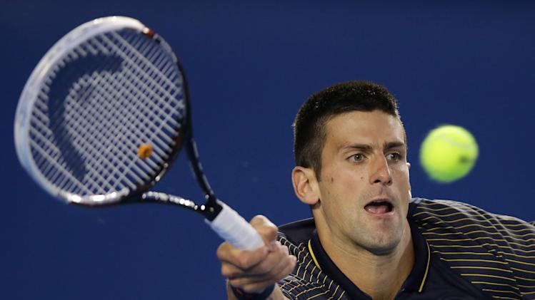 Serbia's Novak Djokovic hits a forehand return to Switzerland's Stanislas Wawrinka during their fourth round match at the Australian Open tennis championship in Melbourne, Australia, Sunday, Jan. 20, 2013. (AP Photo/Dita Alangkara)