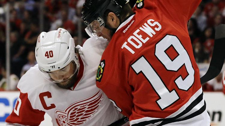 Detroit Red Wings' Henrik Zetterberg (40) battles for the puck against Chicago Blackhawks' Jonathan Toews (19) during the first period of Game 1 of an NHL hockey playoffs Western Conference semifinal in Chicago, Wednesday, May 15, 2013. (AP Photo/Nam Y. Huh)