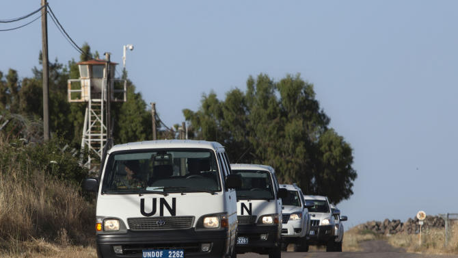 UN vehicles drive into a UN base near the Quneitra crossing between the Israeli-controlled Golan Heights and Syria, Friday, June 7, 2013. Syrian rebels on Thursday briefly captured a crossing point along a cease-fire line with Israel in the contested Golan Heights. (AP Photo/Sebastian Scheiner)