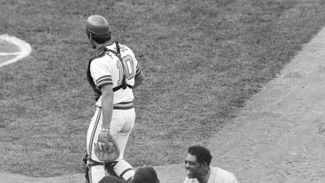 FILE - In this Oct. 14, 1973, file photo, New York Mets' Willie Mays, right, appeals to home plate umpire Augie Donatelli after Donatelli called the Met's Bud Harrelson out at home wile trying to score as Oakland Athletics catcher Ray Fosse heads to the dugout in the 10th inning of Game 2 of baseball's World Series in Oakland, Calif. After Mays pinch hit in Game 3, manager Yogi Berra didn't use him in the final four games of the series.  (AP Photo/File)