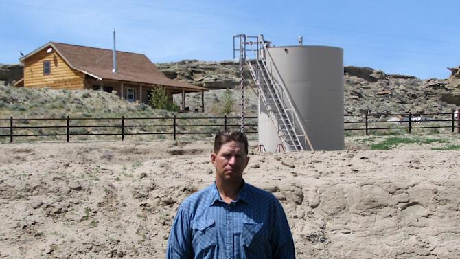 """ADVANCE FOR FRIDAY AMS MAY 4 - FILE - A May 22, 2009 picture shows John Fenton, a farmer who lives near Pavillion in central Wyoming, near a tank used in natural gas extraction, in background. Fenton and some of his neighbors blame hydraulic fracturing, or """"fracking,"""" for fouling their well water. The U.S. Environmental Protection Agency drew skepticism and mistrust from Wyoming regulators after it privately briefed them more than a month in advance about its first-ever public announcement that hydraulic fracturing, a controversial but favored method for releasing difficult pockets of oil and gas, might have caused groundwater pollution. (AP Photo/Bob Moen, File)"""