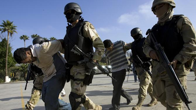 FILE - This Dec. 3, 2008 file photo shows Mexican Army soldiers holding two suspects, arrested during an operation against drug smuggling and kidnapping gangs, after being presented to the press in Tijuana, Mexico. U.S. officials say the Pentagon is stepping up aid for Mexico's bloody drug war with a new U.S.-based special operations headquarters to teach Mexican security forces how to hunt drug cartels the same way special operations teams hunt al-Qaida.  (AP Photo/Guillermo Arias, File)