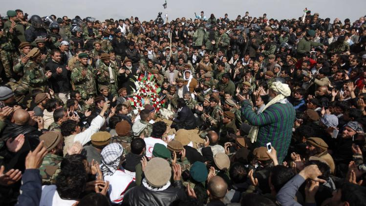 Afghans pray over the grave of Afghan Vice-President Marshal Fahim after he was buried in Kabul