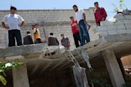 Residents from Kfar Sijna look at the roof of a house, allegedly damaged after a tank shell was fired by Syrian government forces based in nearby Khan Sheikhun, in the north of Idlib province. Western nations want a 10-day deadline set for Syria&#39;s President Bashar al-Assad to halt the use of heavy weapons or face sanctions, according to a draft resolution sent to UN Security Council members