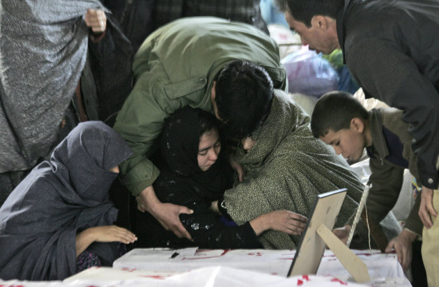 A Pakistani Shiite Muslim woman is comforted while grieving next to the body of her relative, a victim of Saturday's bombing that killed scores of people, as relatives refuse to bury their dead in a p
