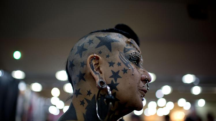 Gaby Peralta attends her sales stand during the 10th annual Buenos Aires Tattoo Show in Buenos Aires, Argentina, Friday, March 7, 2014. The Tattoo Show, which will run from March 7 - 9, is one of the largest events in Latin America dedicated the art. (AP Photo/Natacha Pisarenko)