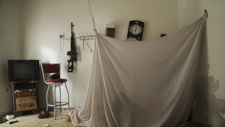 A rebel fighter rests inside a room at Karm al-Tarab frontline in Aleppo
