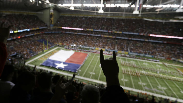 A Texas fans holds up the hook'em horns sign as the Texas band and Texas flag take the field prior to the Alamo Bowl NCAA football game between Texas and Oregon State, Saturday, Dec. 29, 2012, in San Antonio.  (AP Photo/Eric Gay)