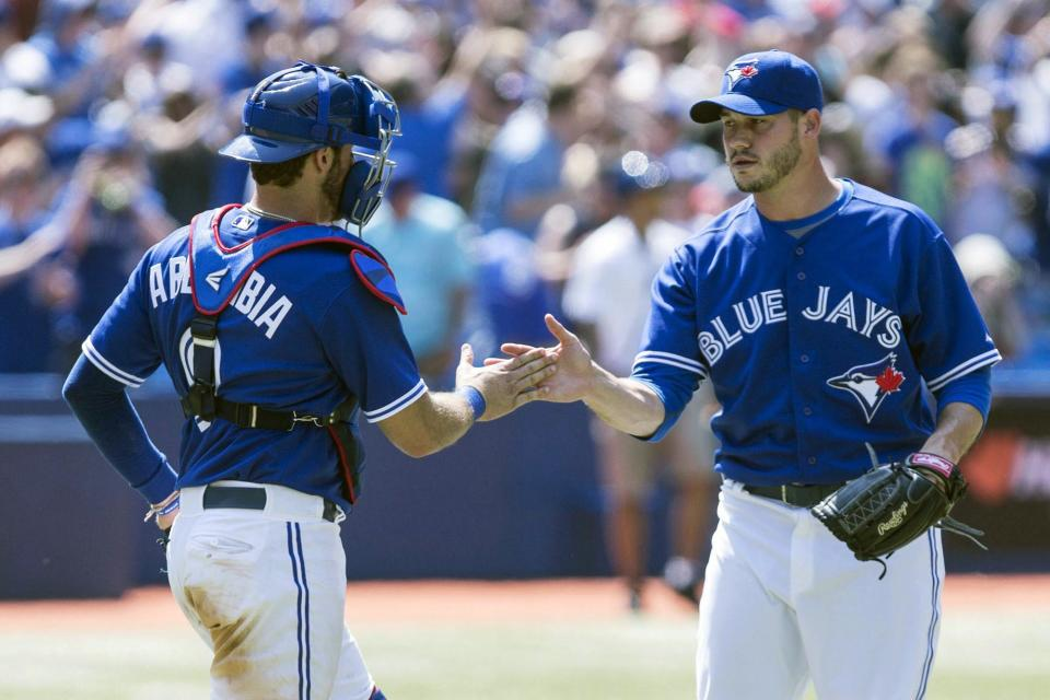 Toronto Blue Jays pitcher Dustin McGowan, right, is congratulated by catcher J.P. Arencibia after a 13-5 win over the Baltimore Orioles in a baseball game in Toronto, Sunday June 23, 2013. (AP Photo/The Canadian Press, Chris Young)