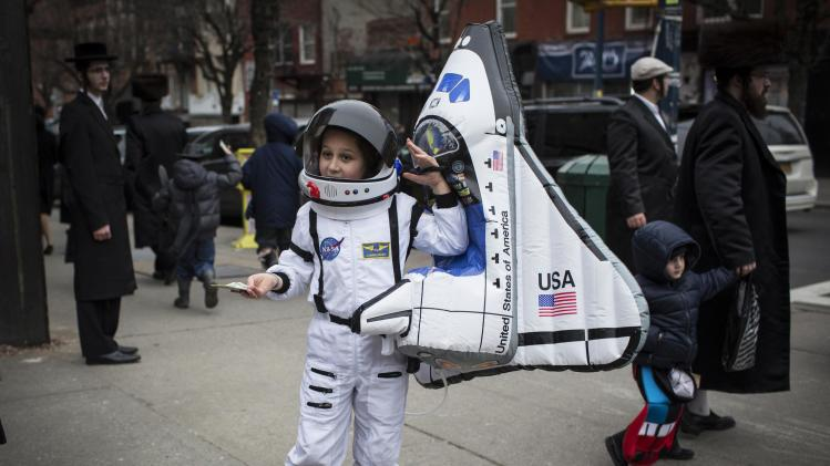 A child dressed as an astronaut stands on a street corner during the Jewish holiday of Purim in the South Williamsburg suburb of New York