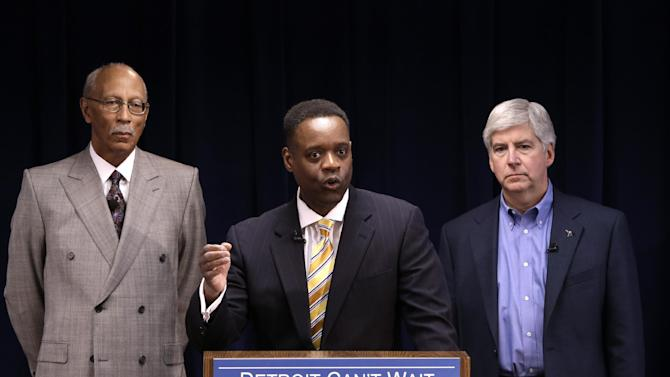 Kevyn Orr, center, speaks at a news conference as Detroit Mayor Dave Bing, left, and Gov. Rick Snyder listen in Detroit, Thursday, March 14, 2013. Snyder announced that he had chosen Kevyn Orr, a partner in the Cleveland-based law and restructuring Jones Day firm, as Detroit's emergency manager. Snyder's already declared a financial emergency in Detroit, saying local officials lacked a plan to solve it. (AP Photo/Paul Sancya)