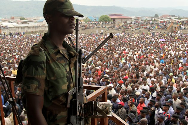 A soldier from the M23 rebel group looks on as thousands of Congolese people listen during an M23 rally, in Goma, eastern Congo, Wednesday, Nov. 21, 2012. Thousands of Congolese soldiers and policemen defected to the M23 rebels Wednesday, as rebel leaders vowed to take control of all Congo, including the capital Kinshasa. The rebels organized a rally at Goma's Stadium of Volcanoes after seizing control of the strategic city in eastern Congo Tuesday. (AP Photo/Marc Hofer)