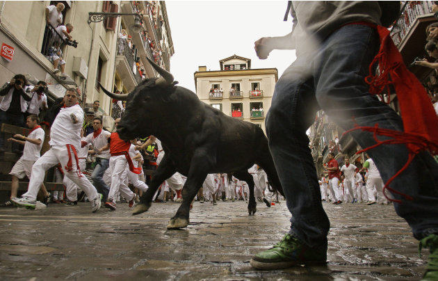 Revelers run on the Estafeta corner as a fighting bull from Miura ranch go on the way during the second running of the bulls at the San Fermin fiestas, in Pamplona northern Spain, Sunday, July 8, 2012.