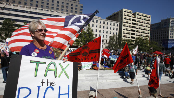 """FILE - In this Oct. 6, 2011 file photo, Carol Gay, of Brick, N.J., holds a sign saying """"Tax the Rich,"""" as several groups including the Peoples Uprisings, October 2011 Coalition, and Occupy DC, """"occupy"""" Freedom Plaza in Washington. The income gap between the rich and everyone else is large and getting larger, while middle-class incomes stagnate. That's raised concerns that the nation's middle class isn't sharing in economic growth as it has in the past. And it sparked the Wall Street protests that spread to other cities in the country. (AP Photo/Jacquelyn Martin, File)"""