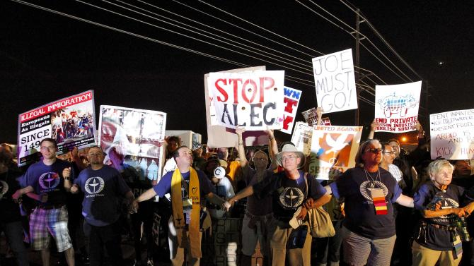 """Demonstrators gather outside a Maricopa County Sheriff's Office jail, called """"Tent City"""", Saturday, June 23, 2012, in Phoenix. Critics of Maricopa County Sheriff Joe Arpaio gathered Saturday night for a rally to call for the closure of the sheriff's complex of canvas jail tents. (AP Photo/Matt York)"""