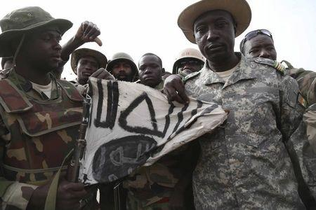 Nigerien soldiers hold up a Boko Haram flag they had seized in the recently retaken town of Damasak