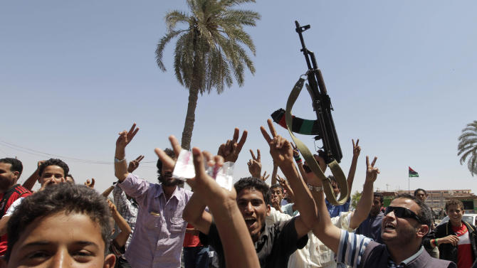 Libyans celebrate after receiving the news of an arrest warrant issued against Moammar Gadhafi, in the rebel-held capital Benghazi, Libya, Monday, June 27, 2011.  The International Criminal Court (ICC) has issued arrest warrants for Libyan leader Moammar Gadhafi, his son and his intelligence chief for crimes against humanity in the early days of their struggle to cling to power. (AP Photo/Hassan Ammar)